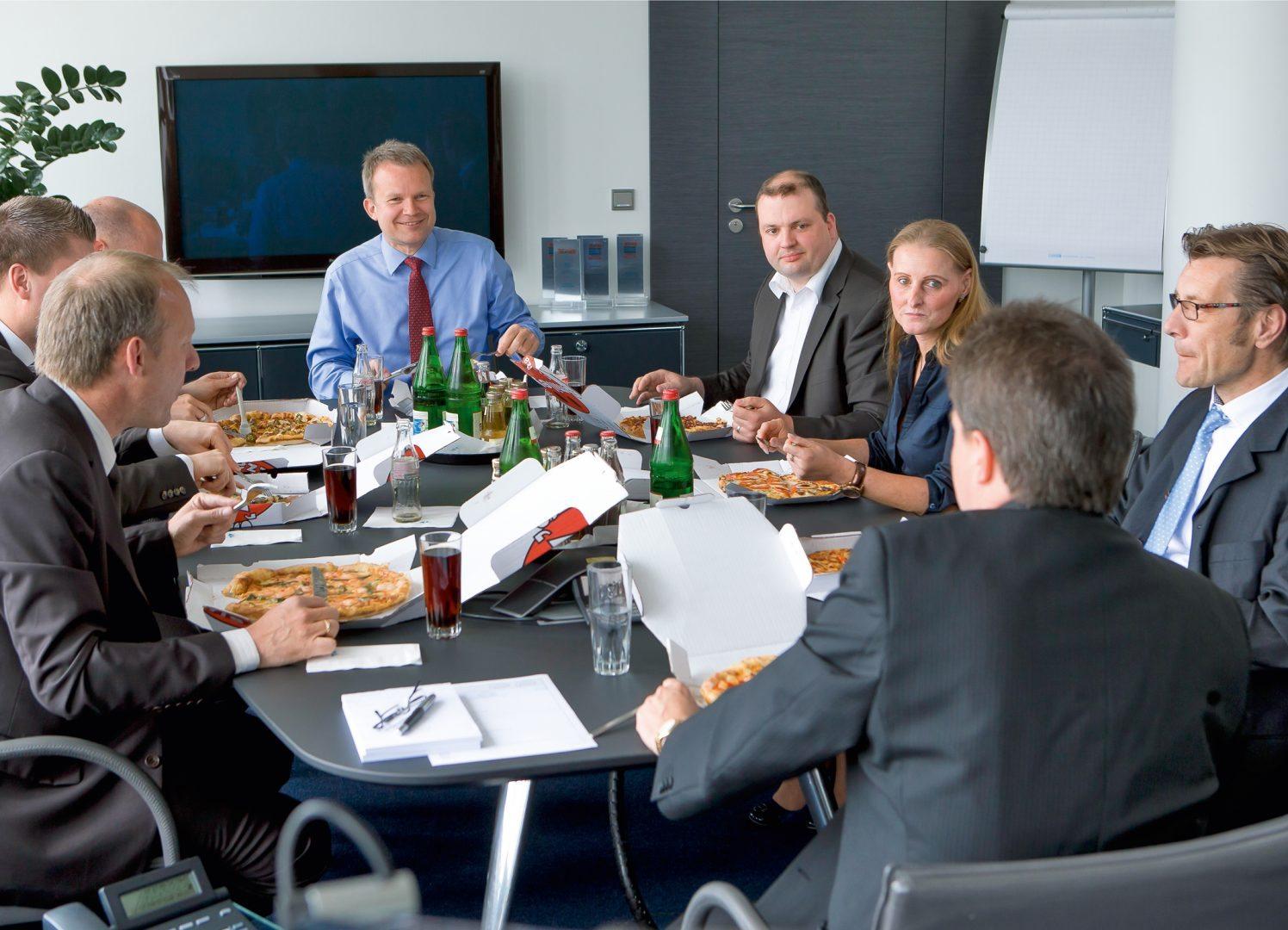 Dr. Jens Baas, TK-Vorstandsvorsitzender (Mitte), mit Mitarbeitern beim Pizza-Treff. Pressefoto der Techniker Krankenkasse zur Verwendung für redaktionelle Zwecke.