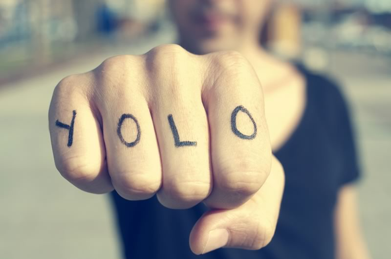Millenial market research Fist with YOLO written on the fingers
