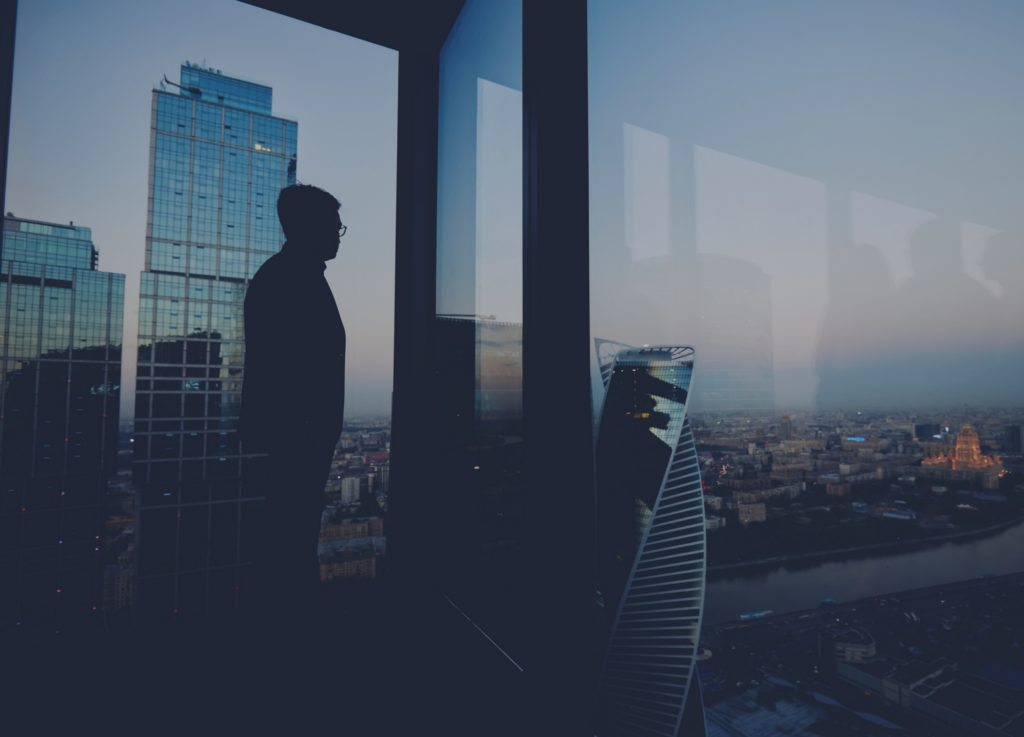 A man staring out over a city thinking about how he can develop himself